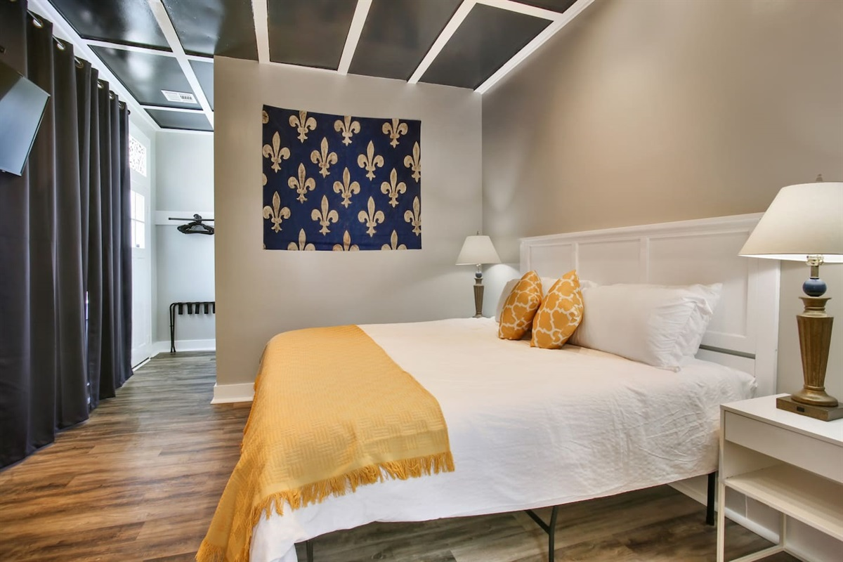 """Bedroom 1, rear of house. 1 king bed, huge windows w/ afternoon sun, blackout curtains, 39"""" cable tv, dresser, luggage rack. Jack & Jill bathroom."""
