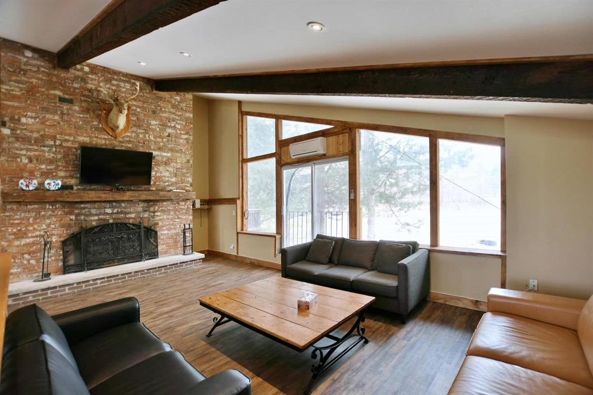 """Spacious living room with wood fireplace, 55"""" 4K TV and 3 large couches"""