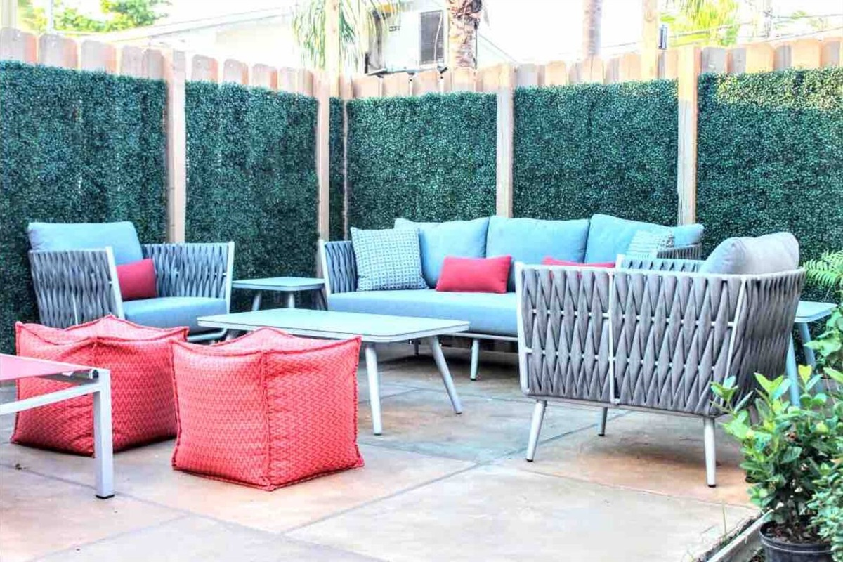 Lounge or picnic in your own patio surrounded by a warm wood fence wrapped in artificial boxwood greens for complete privacy. All seat cushions have a mesh on the bottom to keep the tops as dry as possible at all times.