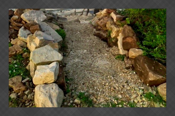 Path to a secluded pebble beach and kayak launch area.