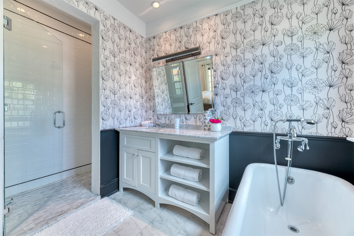 """We love our """"Art Deco"""" bathroom with the deep black bath and gorgeous wallpaper. Hanging from the ceiling is a vibrant red light fixture. Beautiful vanity & mirror bring in style and amazing walk in shower!"""