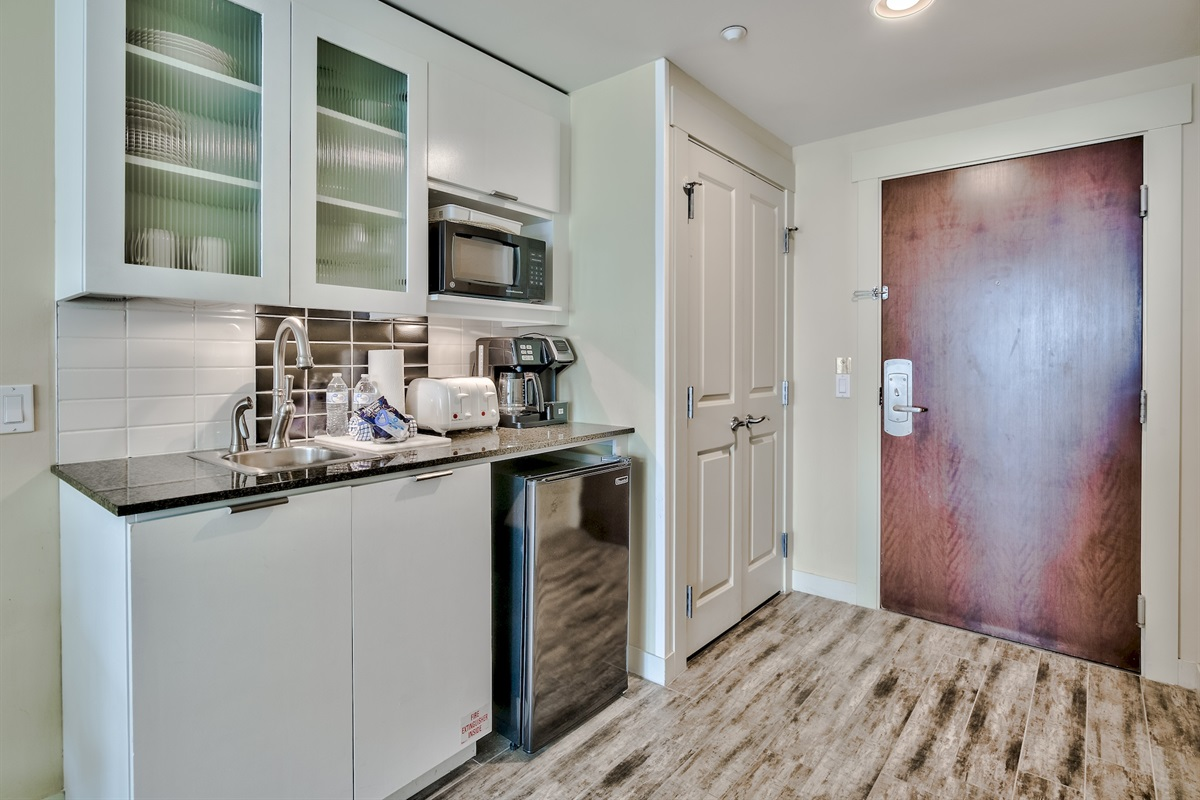Kitchenette with mid size fridge, coffee machine, microwave, toaster and blender.