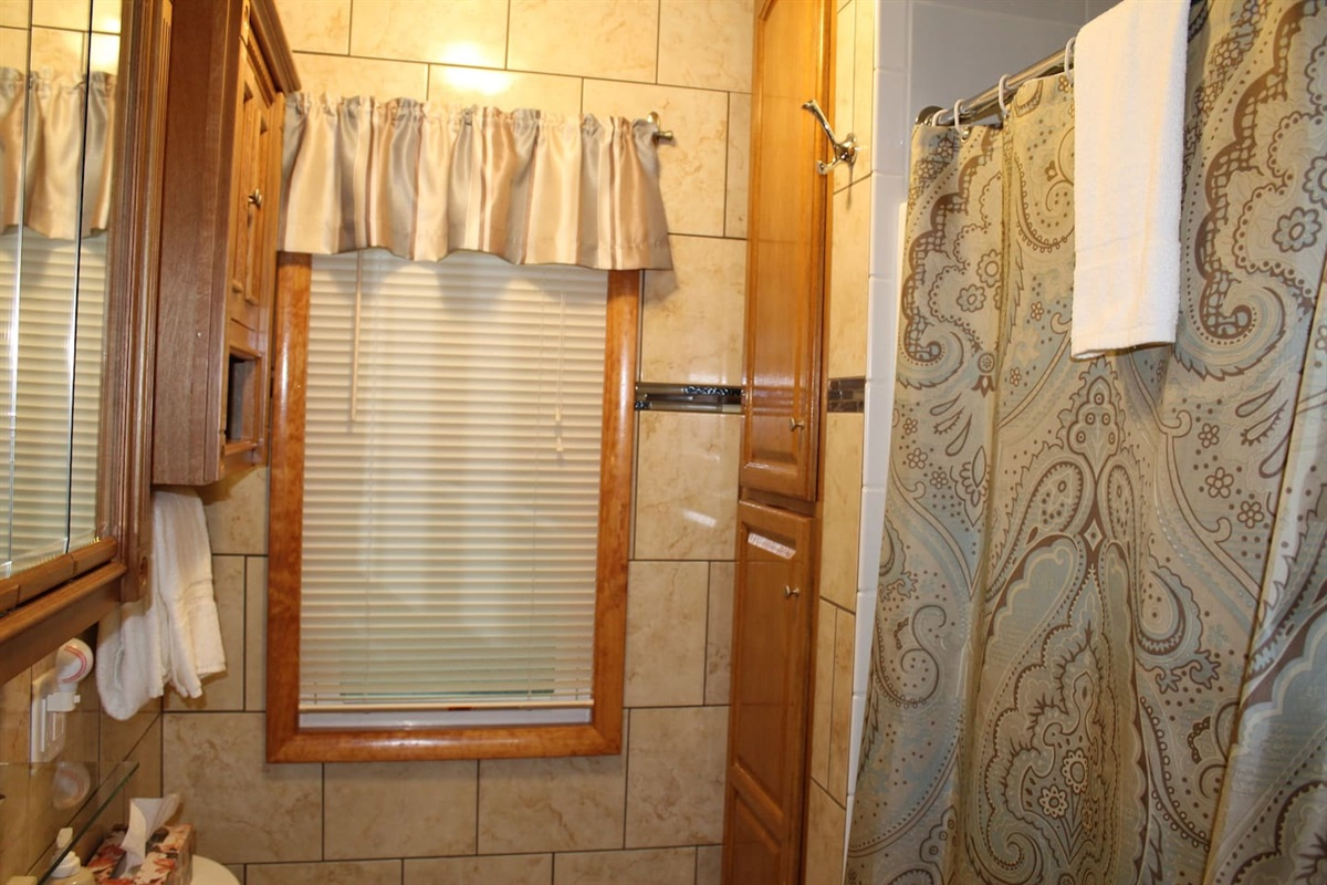 Fully tiled bathroom on the main floor with stall shower