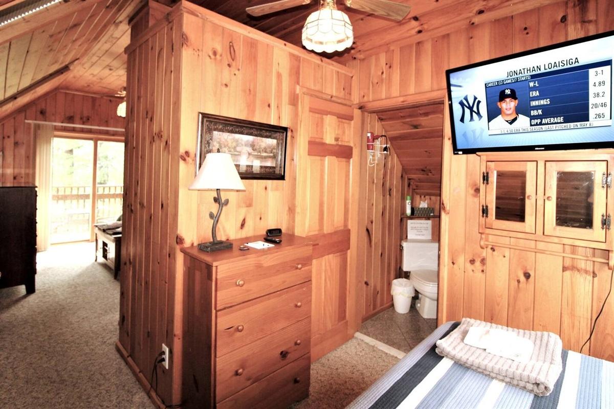 Flat screen smart Roku TV in twin bedroom, with half bath.