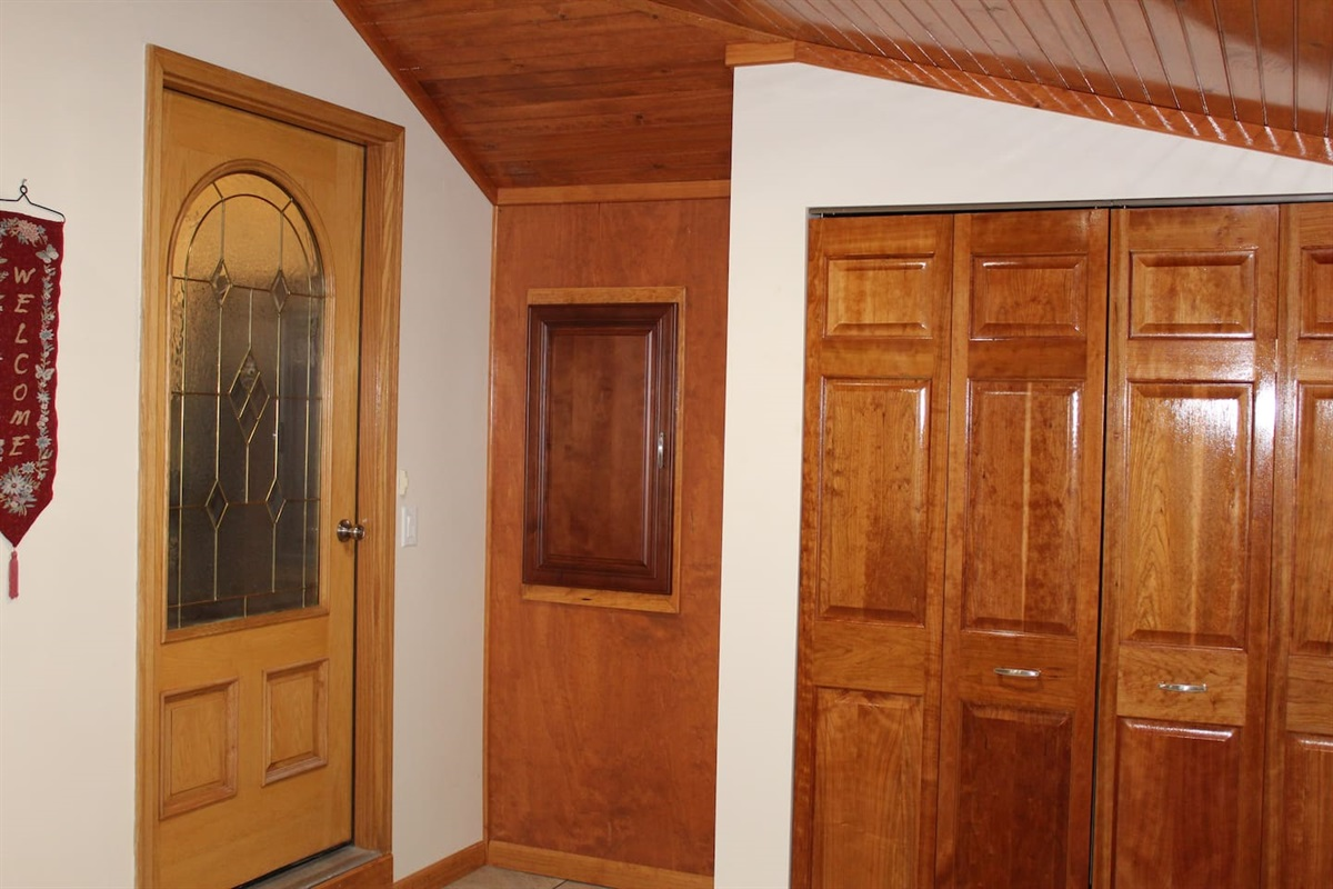 Foyer entry with cherry wood doors on the closet.