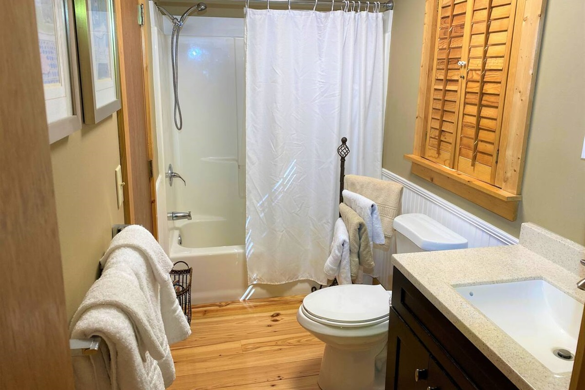 Main level bathroom has entrances off the kitchen as well as the master bedroom.
