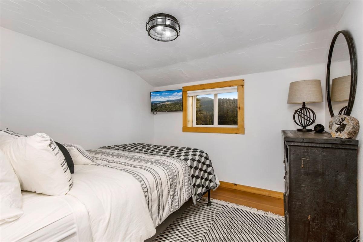 Bedroom #2 (Upper Level): Bedroom has mountain views, TV, dresser, and 1 queen bed.