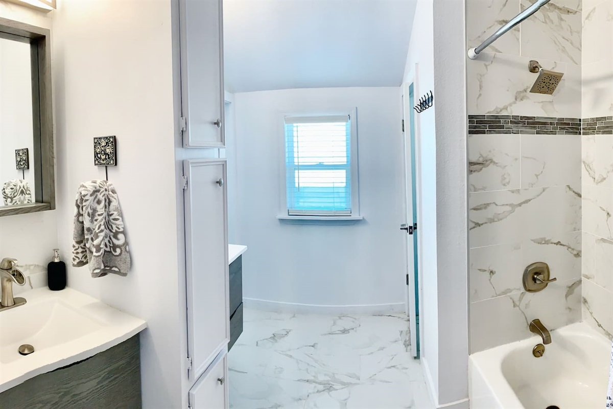 Newly renovated marble bath w/ dual sinks, shower/tub combo and private water closet