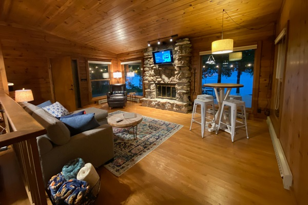 The intimate living room space features a beautiful Door County stone fireplace and water views.