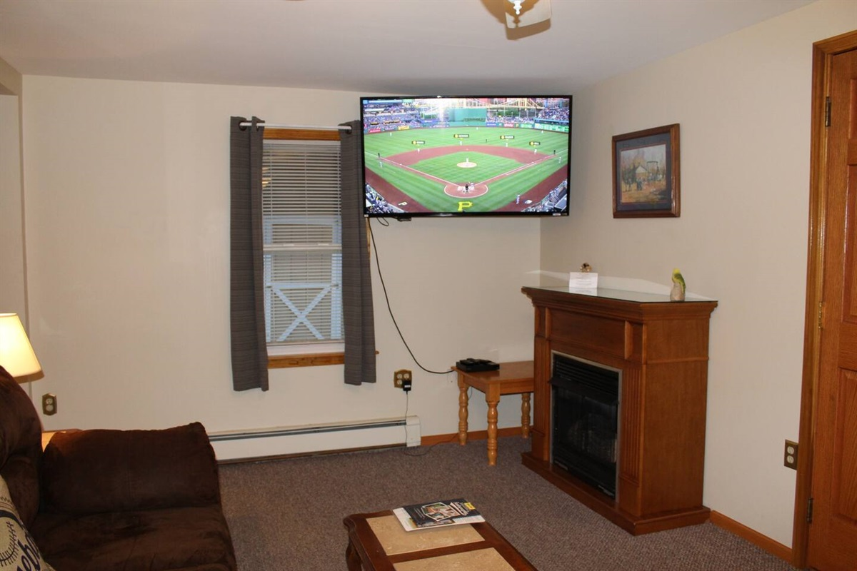 """Large living room with 55"""" (or larger) flat screen smart TV with Roku.  Bring your favorite streaming app and never miss one of your favorite shows!  (New hardwood floor replaced carpeting in fall 2020 - not pictured)"""
