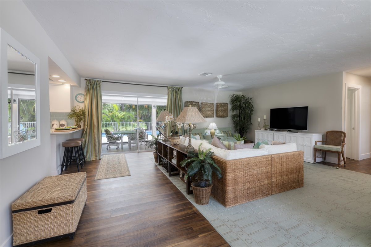 Stylish tropical living with spacious sofas, large Smart App TV, warm and inviting family- style home with pool, remote control candle fireplace, bar, grill and comfort. Warm tones of wood, teals, greens and creams throughout the home.
