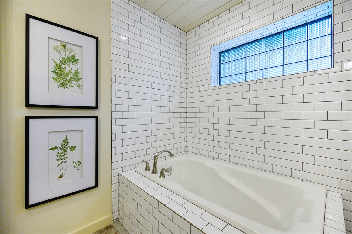 Master bath features a soaking tub and shower enclosure