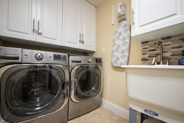 Laundry Room inside condo.  New LG washer/dryer, sink, iron board, & dry rack