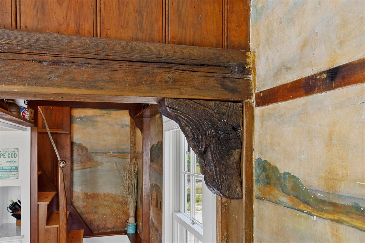 """The main header beam for the bunk loft was salvaged from a shipwreck off the cost of Chatham along with the """"ship's knees"""" and original iron nails which are visible and serve as the corner braces to the loft above."""