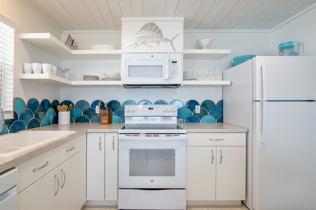 White cottage kitchen with open shelving and fully stocked.