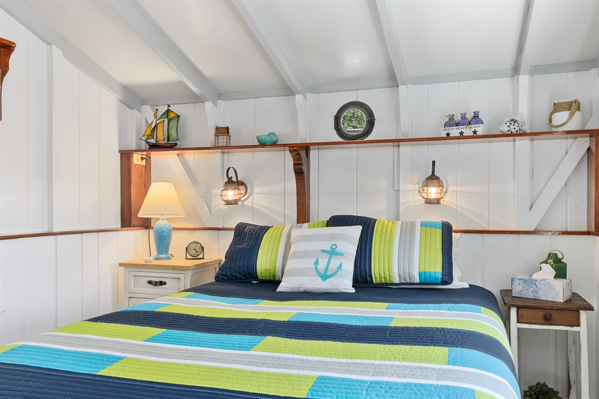 Queen size bed located in the first floor master bedroom. Numerous nautical touches and built-ins throughout the cottage include an original portal window the builder salvaged from a sailing vessel and positioned above the bed.