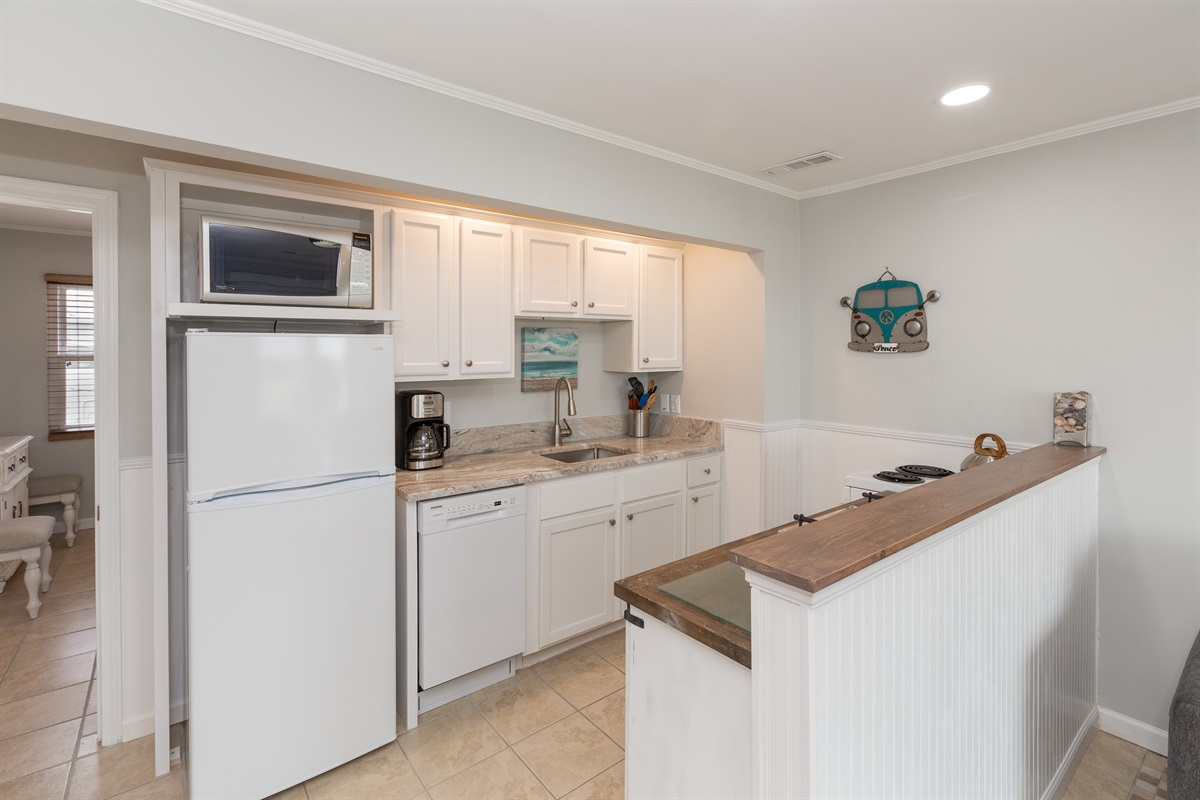 Built in appeal in this kitchen with all essentials including coffee maker, toaster, microwave, stove/oven, and enough pots pans and tools to eat in.