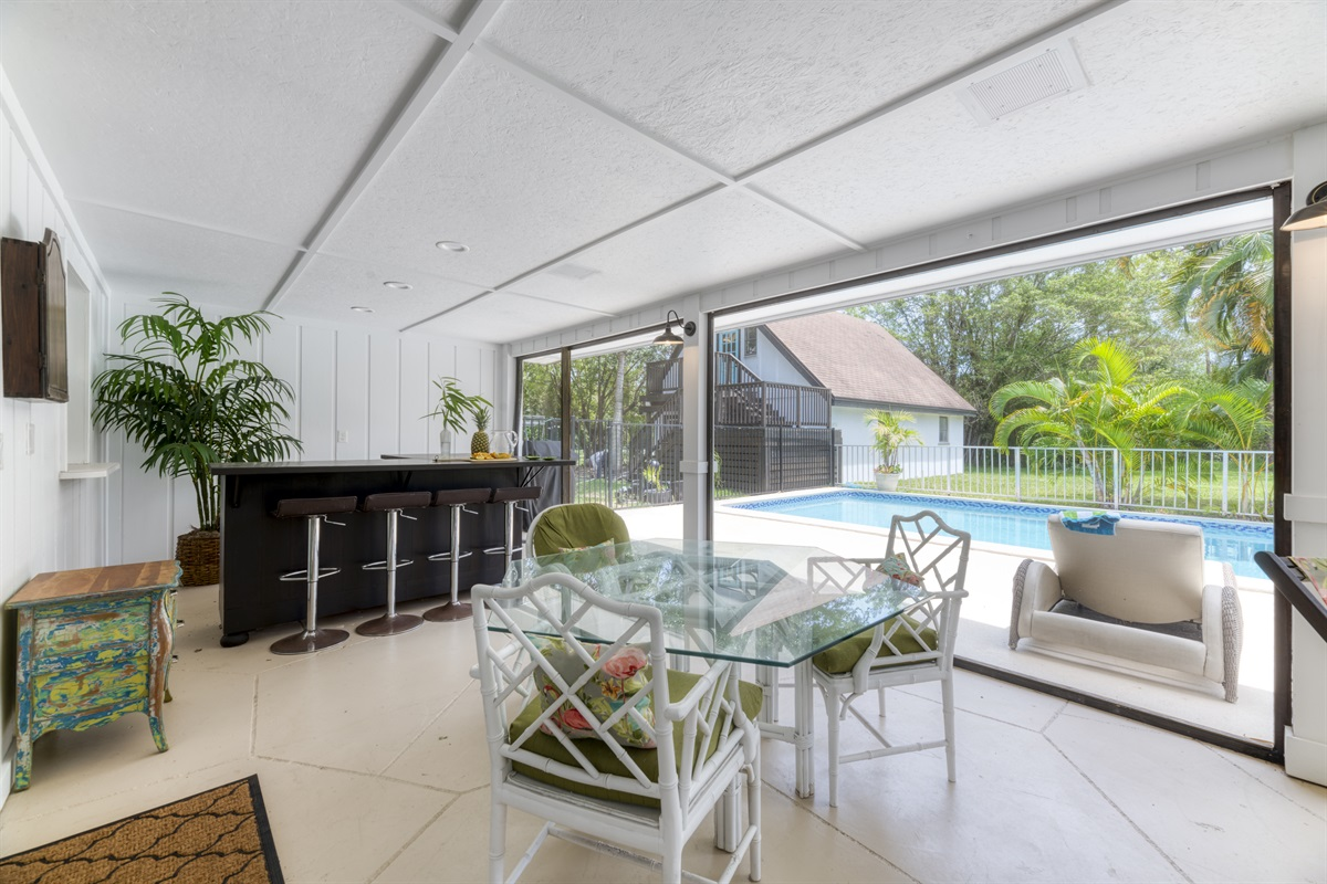 This is paradise! Entertain or relax outdoors with the large outdoor space. Private bar counter with stools, BBQ Grill, glass dining table and ample lounging space. Close the mosquito netting for those warm Florida evenings overlooking the pool.