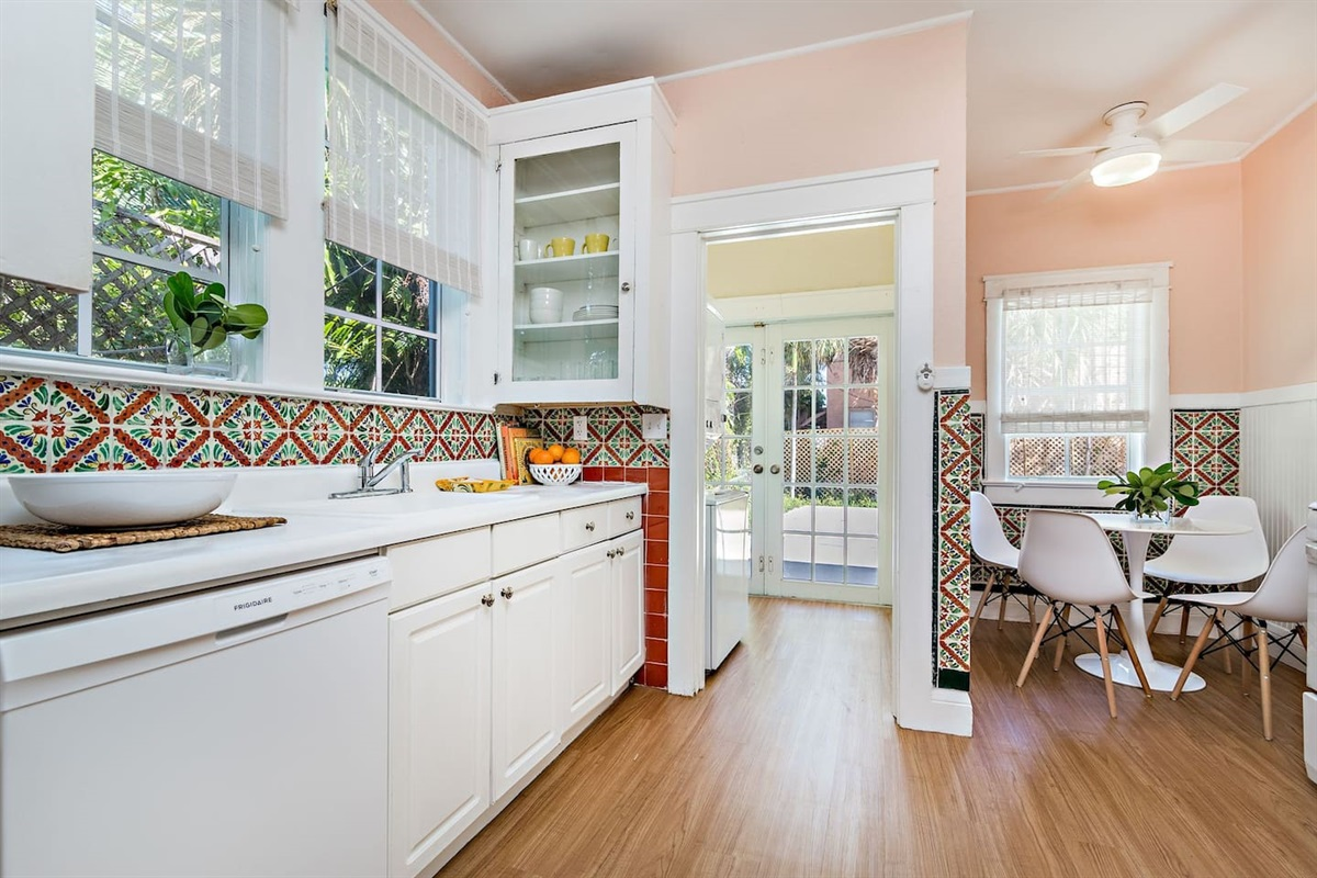 Sweet Country / Spanish style kitchen with original painted floral tiles. White counter tops & appliances, small dining table for 4. Everything you need to feed the hungry crew. Off the kitchen is the washer & dryer.
