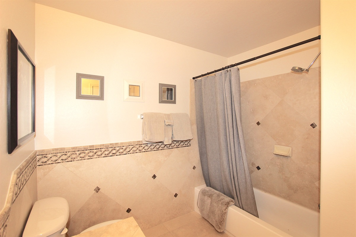Guest bathroom with tub/shower enclosure.