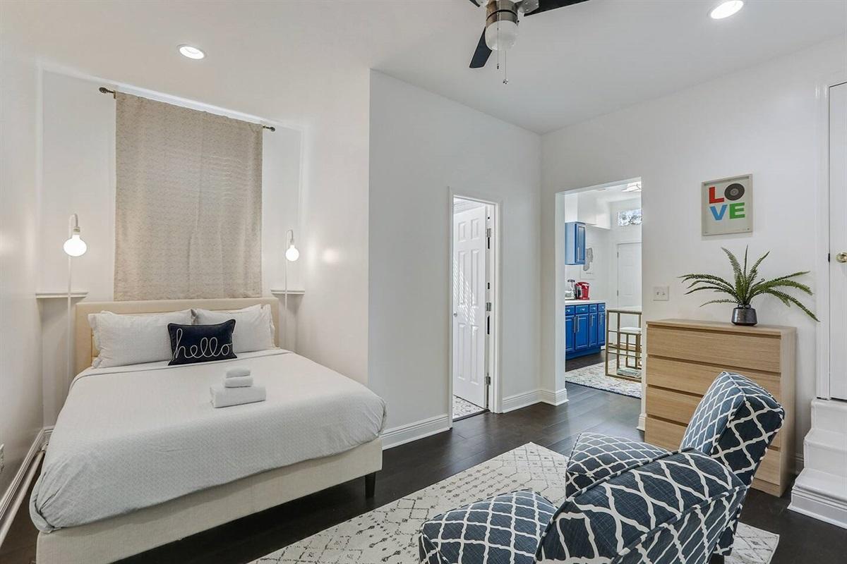 Bedroom. Queen bed looking into kitchen and bathroom.