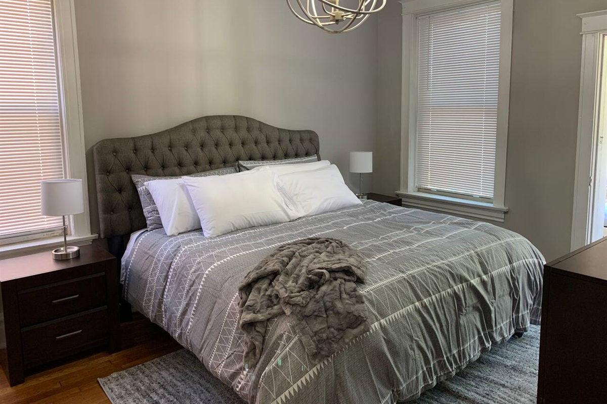 King sized bed with plenty of pillows and a comfy throw for cool nights.