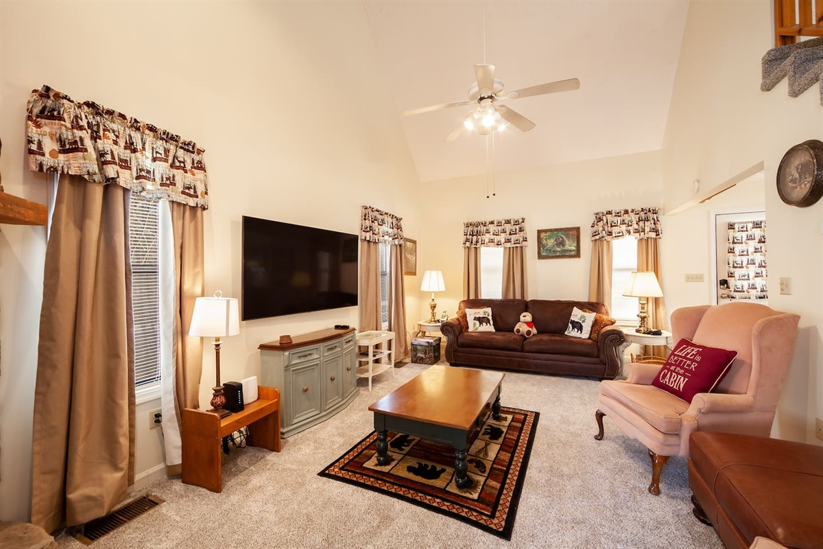"Living room with a 65"" TV  and a fold out sofa for extra guests,"