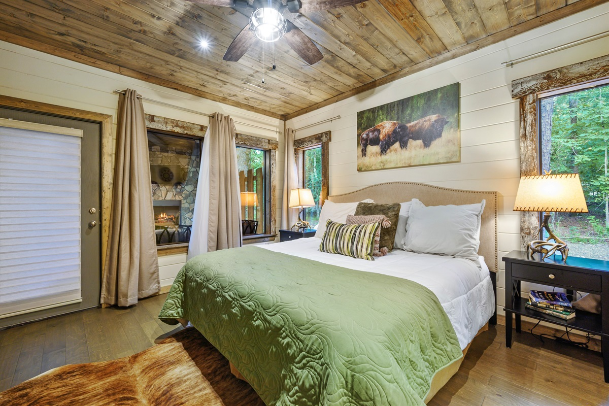 Downstairs bedroom doubles as an additional master suite that is set up just like the master with windows around and rear access to the back porch fireplace and TV sitting area