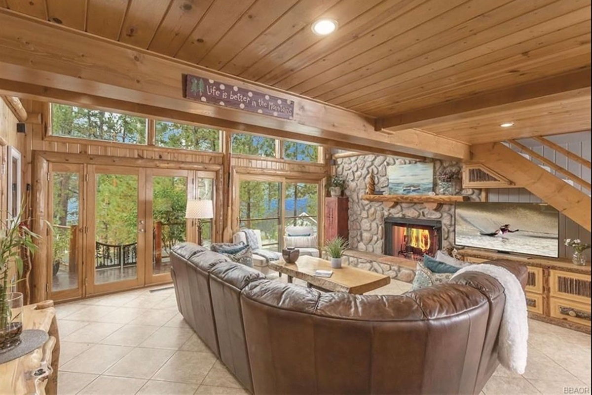 Living Room: Spacious living room with rustic wood burning fireplace, TV, soaring 9+ feet tall ceiling, and wall of windows featuring breathtaking mountain views of Big Bear.