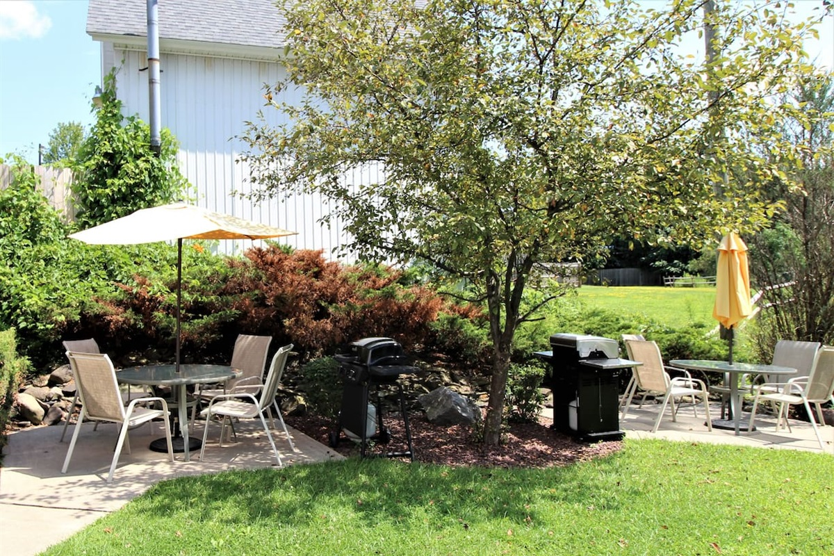 Backyard BBQ area with gas grills and patio dining sets