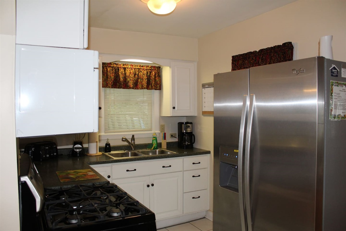 Fully equipped kitchen on the main living level, with stainless steel gas stove, refrigerator with automatic ice maker,  over the range microwave and k-cup/coffee pot combo