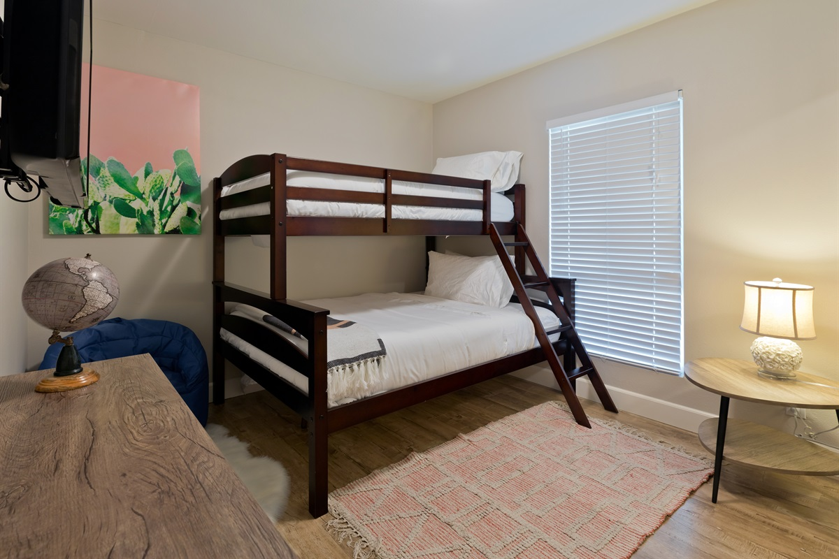The mixed bedroom features a twin over full bunk setup that works perfect for kids or friends. Also included is a bean bag chair, smart TV, and double mirror door closet.