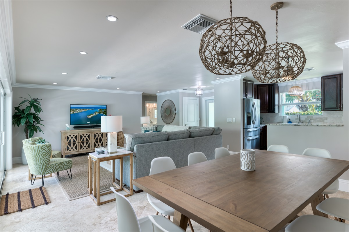 Gorgeous open plan living and dining room area with 10 seater gorgeous wooen table with low hanging rustic light fixtures and direct access to the pool deck.