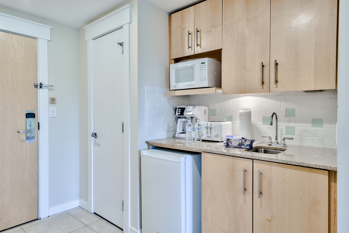 Kitchenette with a combination coffee machine, toaster, microwave and a fridge