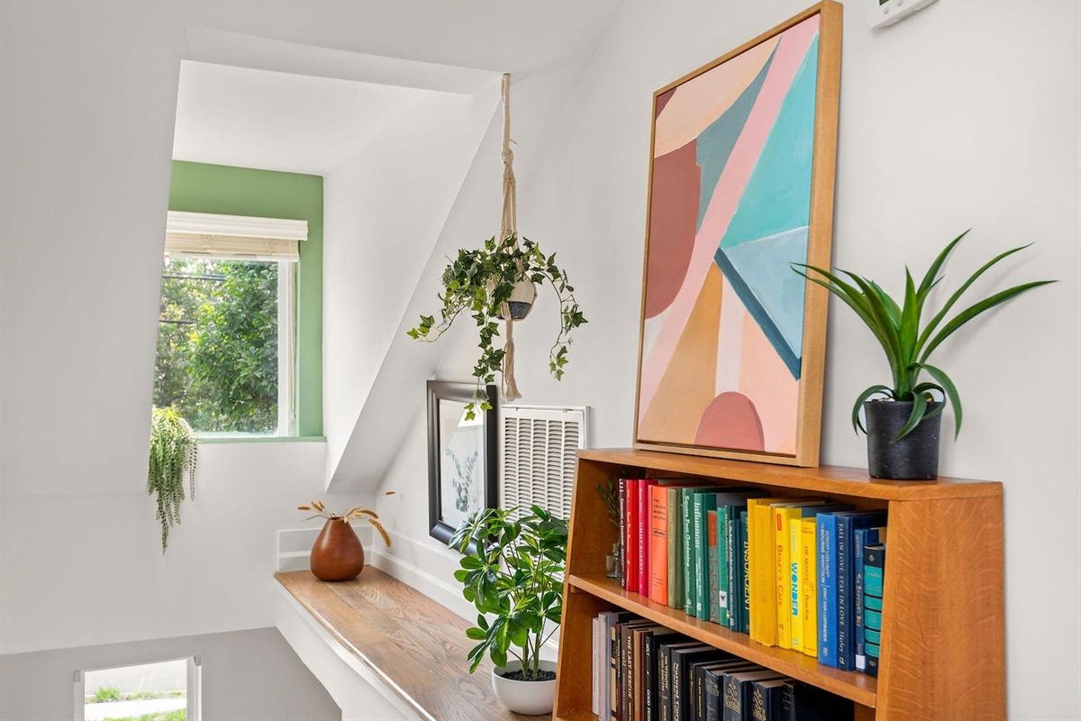 Beautifully decorated stairway with refinished original wood steps and a fully stocked bookshelf