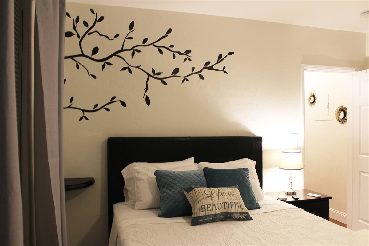 A decorative tree hangs over the bed with a side table and lamp.