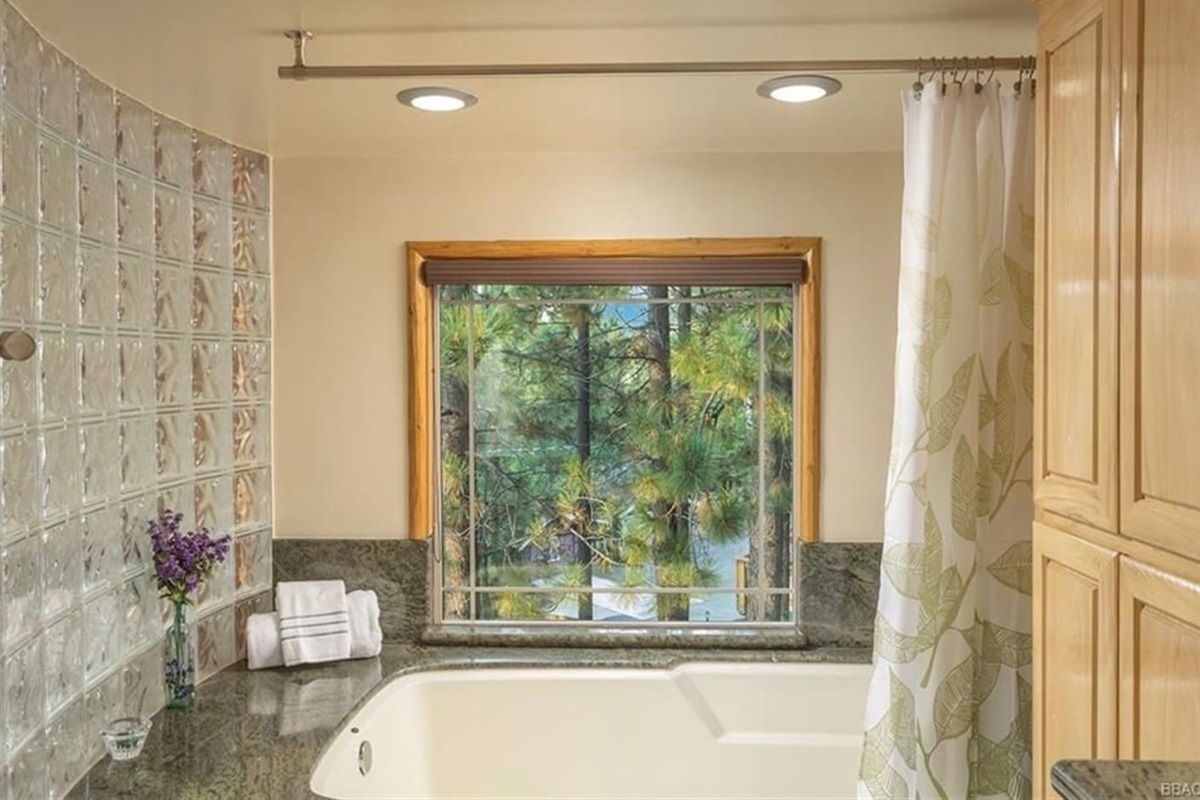 Bathroom #2: Ensuite bathroom to Bedroom #2 with dual sinks, granite countertops, and large soaking tub with shower.