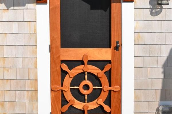 Rear yard entrance with custom mahogany ship's wheel storm door.