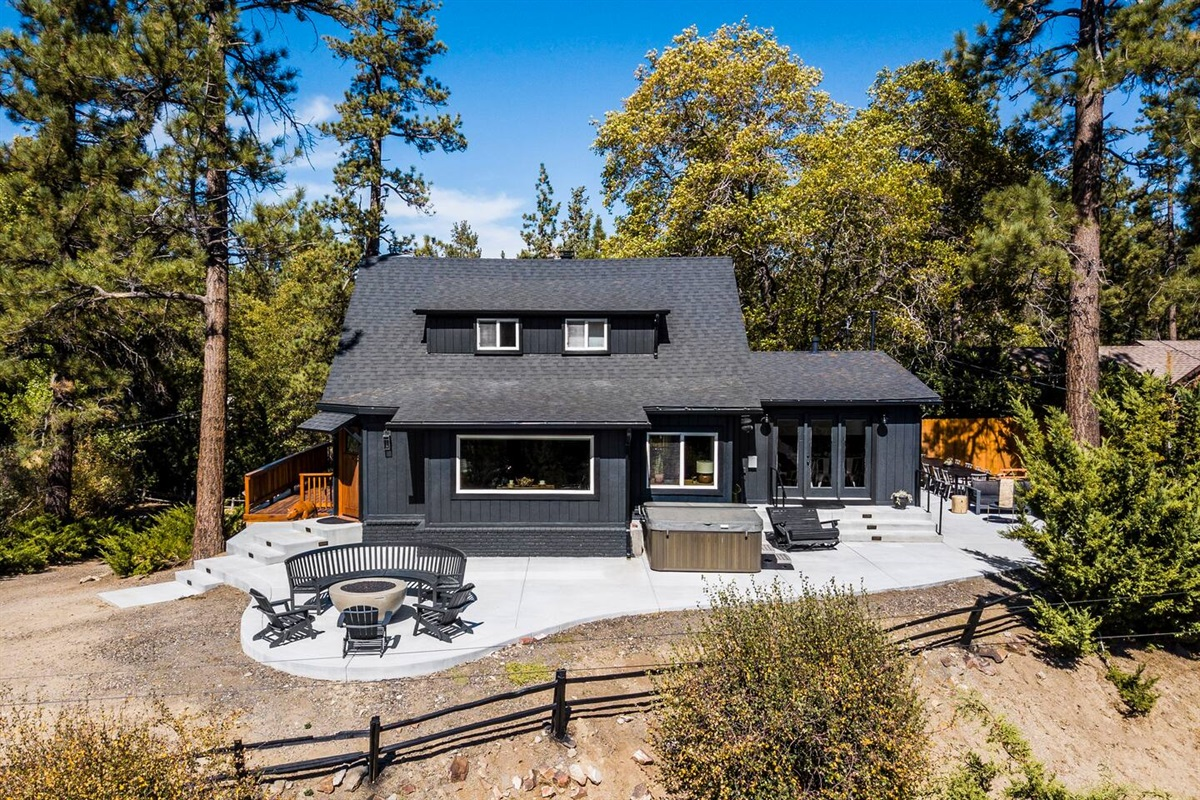 Grand view of spacious back deck with fire pit, hot tub, and outdoor dining area.