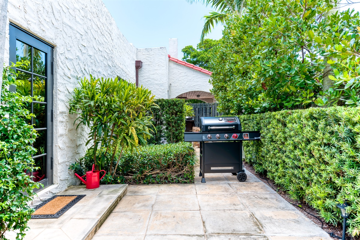 """From the kitchen step outside to the pool deck. There you will find a brand new large 4 Burner grill with all the """"bells and whistles"""". Enjoy the lush tropical resort-style surroundings of the landscaping arounf the pool."""