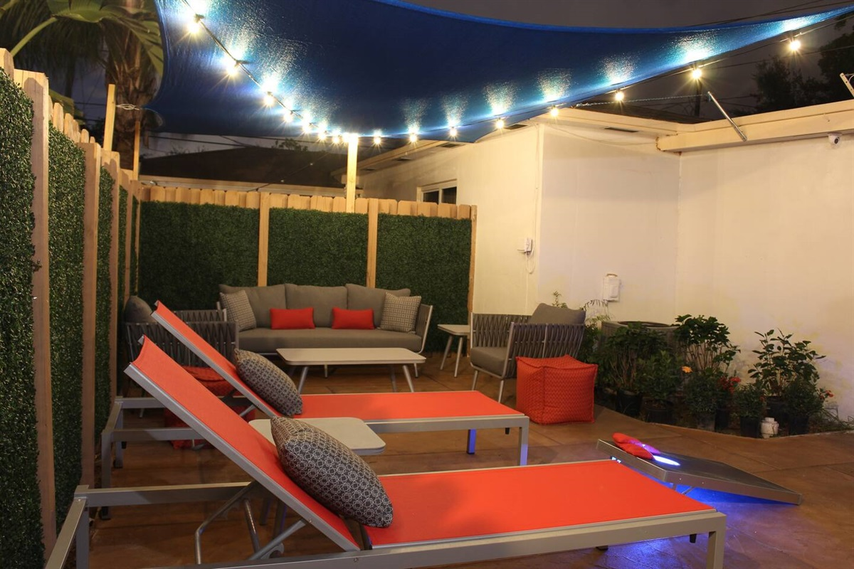 The private patio is located just outside the back door leading out from the kitchen area and can seat up to 8 people. A blue canopy above provides shade during sunny days and the string lights add ambiance to your summer evenings.