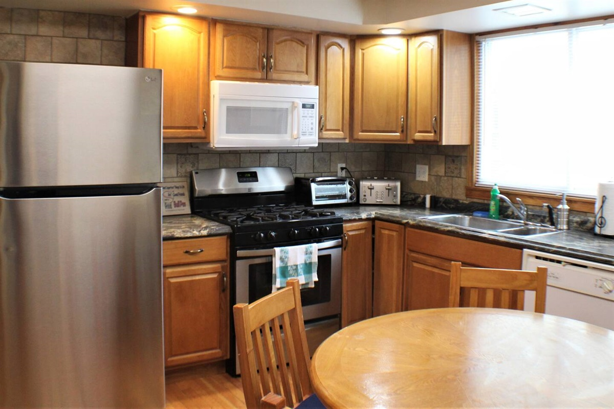 Fully equipped kitchen with hardwood floors and tiled backsplash.  Features a gas range, microwave, dishwasher, and full size refrigerator with automatic ice maker.
