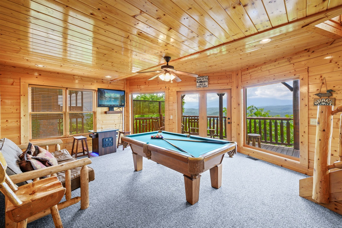Game room has a pool table and an arcade game