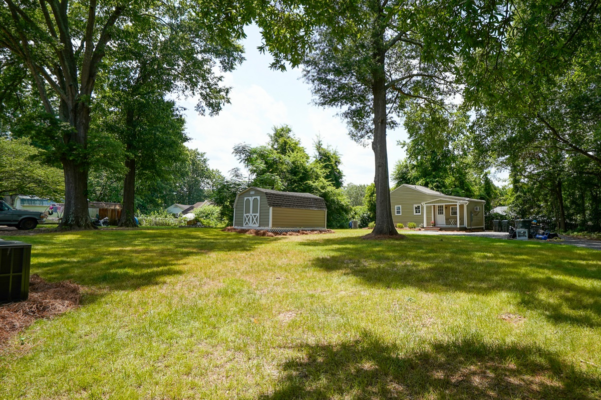 The cottage sits behind the main house and shares a backyard.  It has separate driveways for both properties.